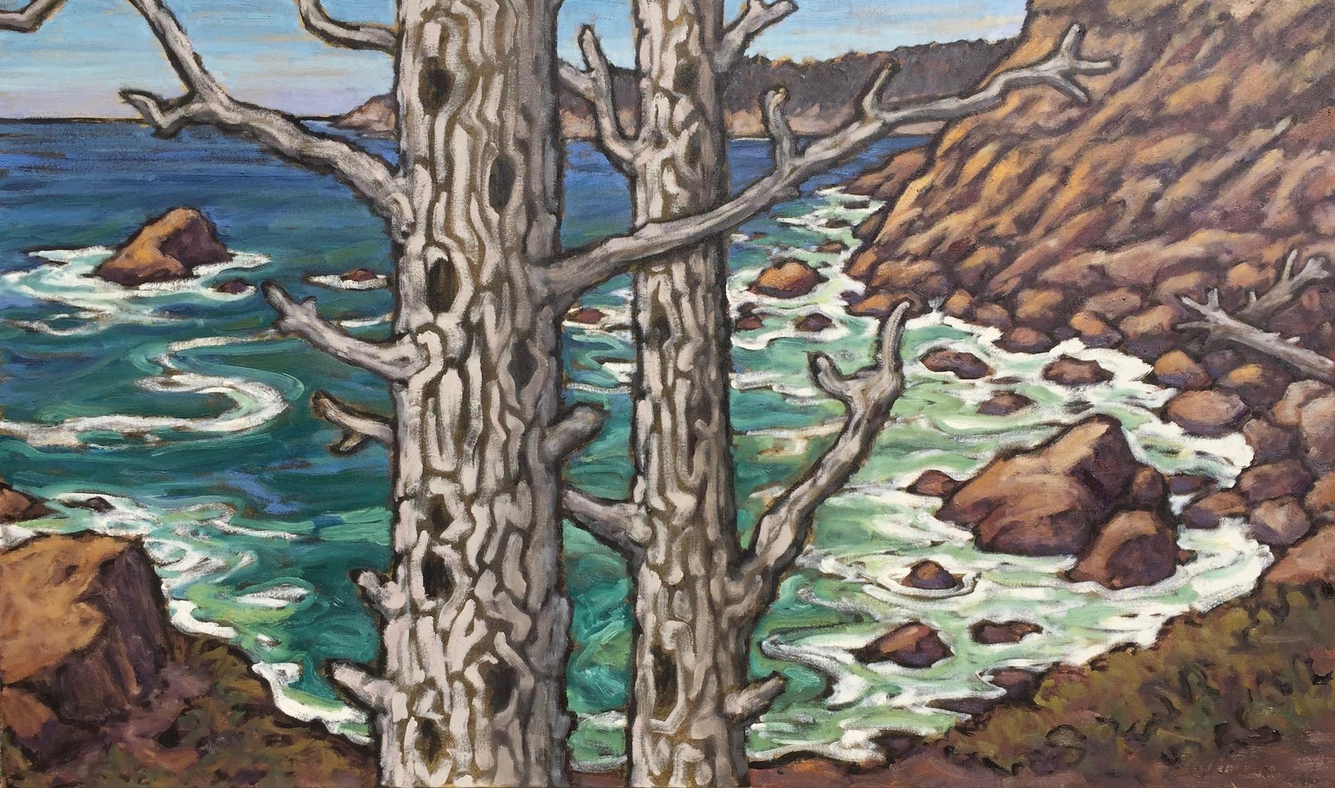 two tree trunks in foreground with rocky coast line in background