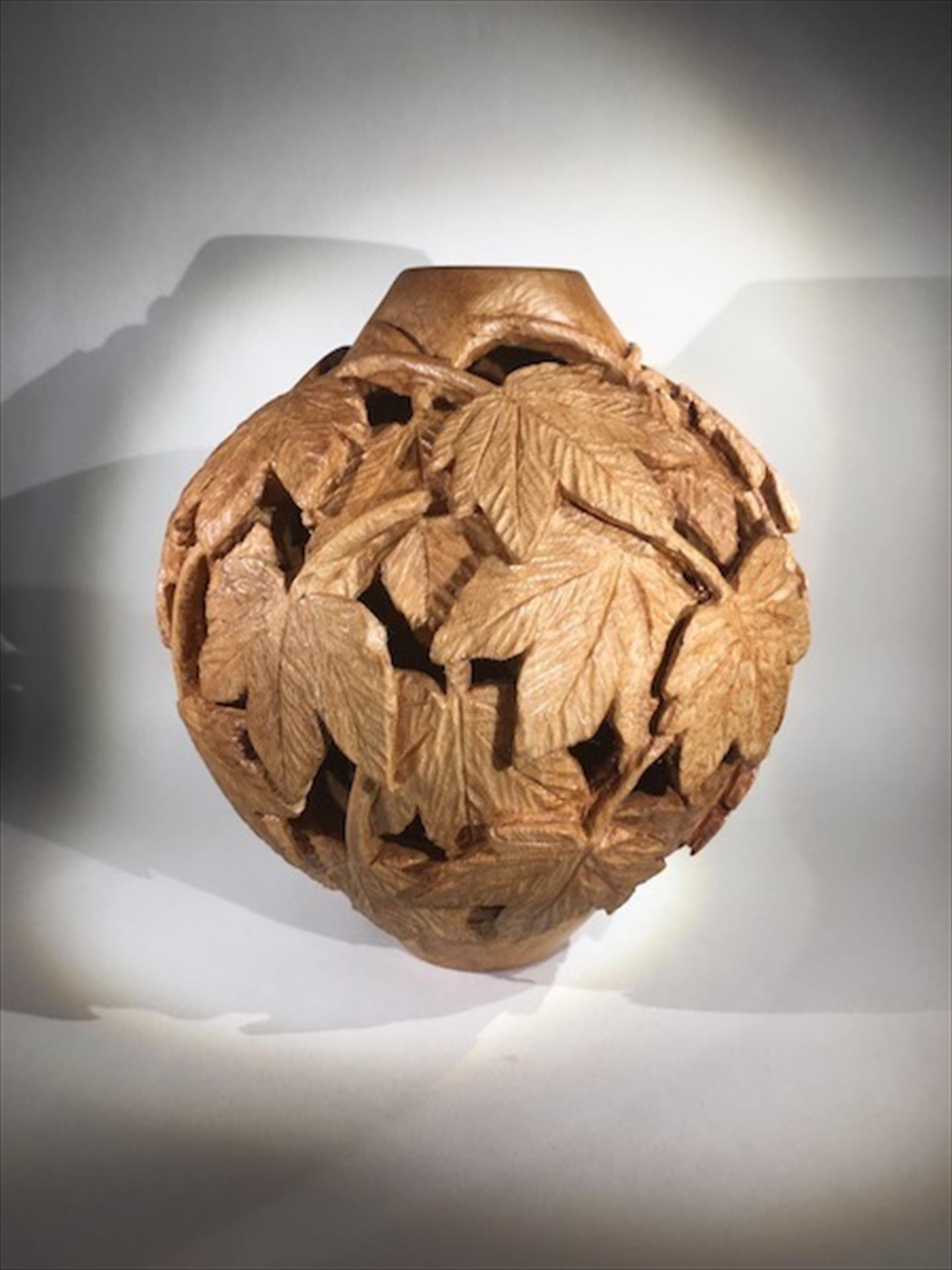 carved wood hollow form with decorative leaves